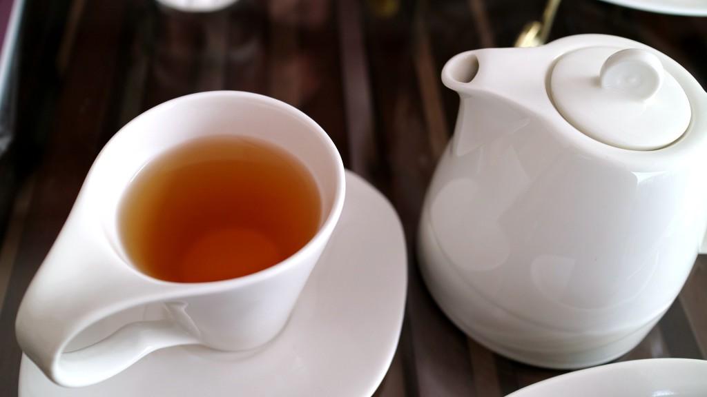 Schwarzer Tee in einer Teetasse serviert - dazu eine Teekanne