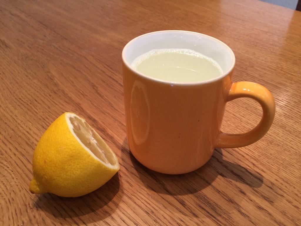 Zitronen Tee in Teetasse mit halber Zitrone garniert