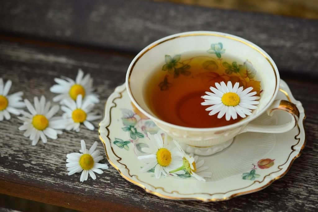 Kamillentee in einer Teetasse mit Blüte garniert